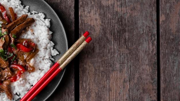 Bovenaanzicht van traditionele aziatische rijstgerecht met vlees en kopie ruimte