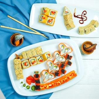 Bovenaanzicht van traditionele japanse keuken set sushi roll met zalm garnalen avocado en roomkaas op blauw en wit