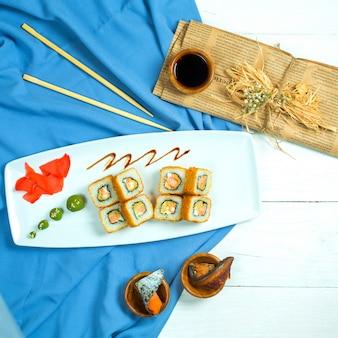 Bovenaanzicht van traditionele japanse keuken sushi roll met zalm avocado en roomkaas op blauw en wit