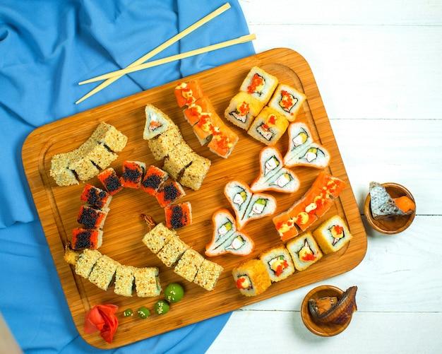 Bovenaanzicht van traditionele japanse keuken sushi roll met zalm avocado en roomkaas op een houten schotel op blauw en wit