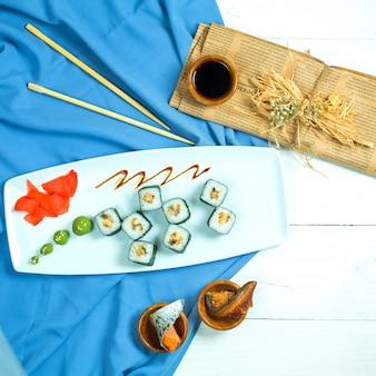 Bovenaanzicht van traditionele japanse keuken zwarte sushi roll met rijstgarnalen roomkaas geserveerd met sojasaus gember en wasabi op blauw en wit