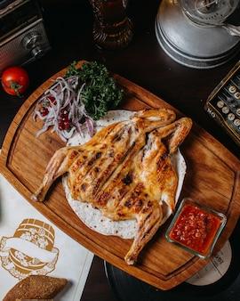Bovenaanzicht van traditionele kaukasische keuken van gegrilde kip tabaka met rode ui kruiden en tomatensaus adjika