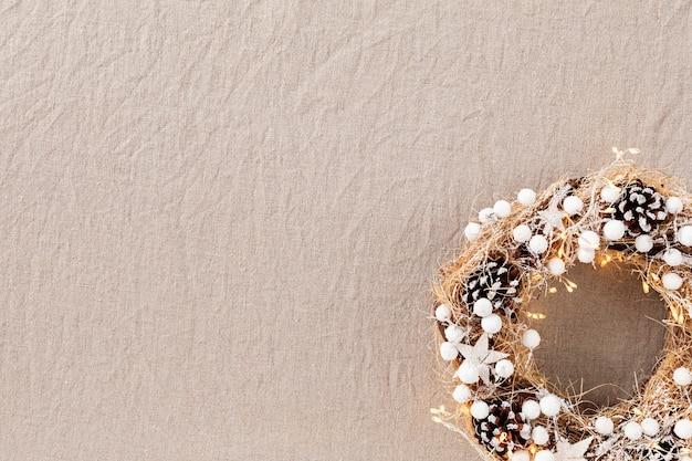Bovenaanzicht van traditionele kerstkrans met kopie ruimte over neutraal linnen weefsel achtergrond. wintervakantie en kerstviering concept