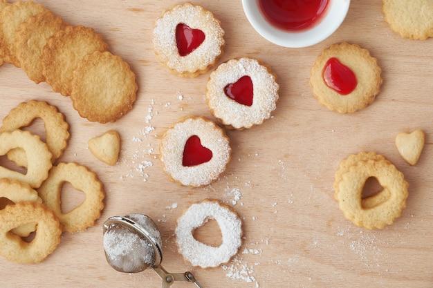 Bovenaanzicht van traditionele linzer-koekjes gevuld met aardbeienjam op een houten bord met hartvormige openingen