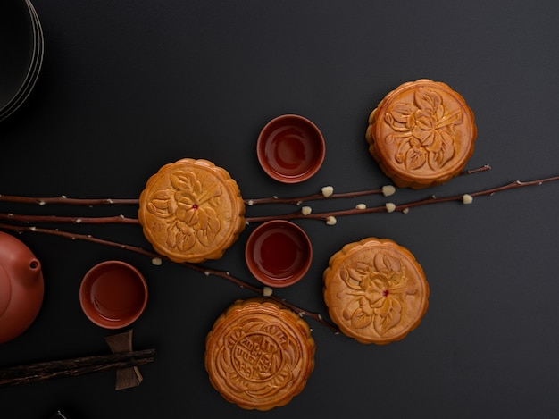 Bovenaanzicht van traditionele maancakes en theekopjes op zwarte tafel met kopie ruimte en decoratie