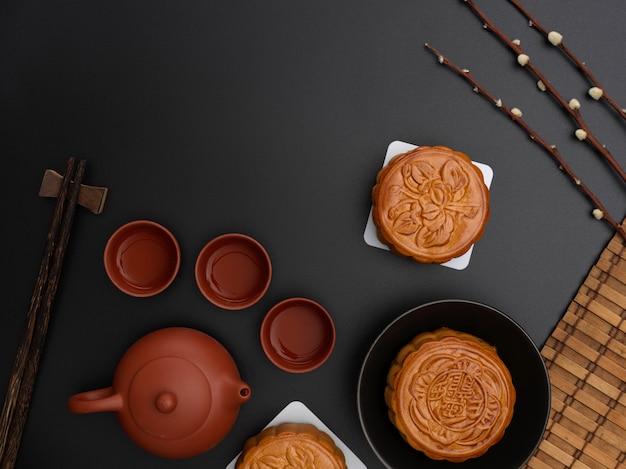 Bovenaanzicht van traditionele maancakes en theeservies op zwarte tafel met kopie ruimte en decoratie. chinees karakter op de maancake vertegenwoordigt