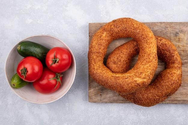 Bovenaanzicht van traditionele turkse bagels op een houten keukenbord met een kom tomaten en komkommers op een witte achtergrond