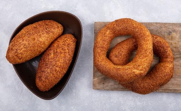 Bovenaanzicht van traditionele turkse bagels op een houten keukenbord met sesampasteitjes op een bruine kom op een witte achtergrond