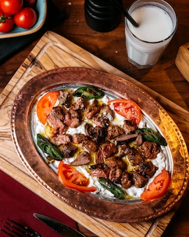 Bovenaanzicht van traditionele turkse iskender doner met yoghurt op plaat