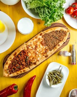 Bovenaanzicht van traditionele turkse keuken turkse pizza pita pide met een andere vulling vleeskaas plakjes kalfsvlees en groenten op een houten tafel