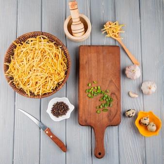 Bovenaanzicht van traditionele zelfgemaakte italiaanse rauwe pasta in een rieten mand mortel houten snijplank met gehakte groene ui en kwarteleitjes op rustieke achtergrond