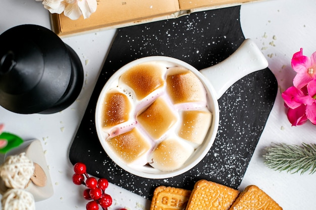 Bovenaanzicht van traditionele zoete aardappel braadpan met marshmallows in geportioneerde vormen op een houten zwarte snijplank