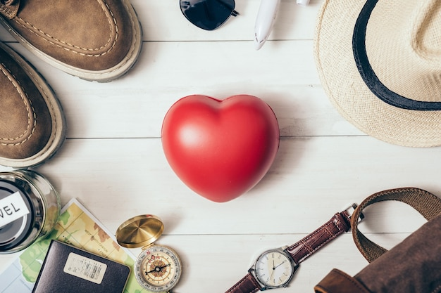 Bovenaanzicht van traveler's accessoires met rood hart in het midden.