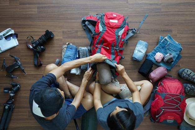Bovenaanzicht van traveler's young paar rugzak planning