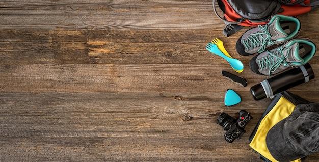 Bovenaanzicht van trekkinguitrusting in hoek op houten achtergrond met kopie ruimte, bovenaanzicht