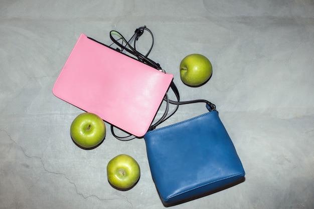 Bovenaanzicht van trendy blauwe en roze lederen handtassen gerangschikt op tafel met verse groene appels met concept van milieuvriendelijke materialen