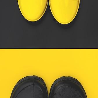Bovenaanzicht van trendy heren en dames rubberen laarzen op contrasterende achtergronden. concept van de herfst en liefde. copyspace.