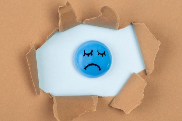 Bovenaanzicht van trieste ballon in gescheurd papier voor blauwe maandag