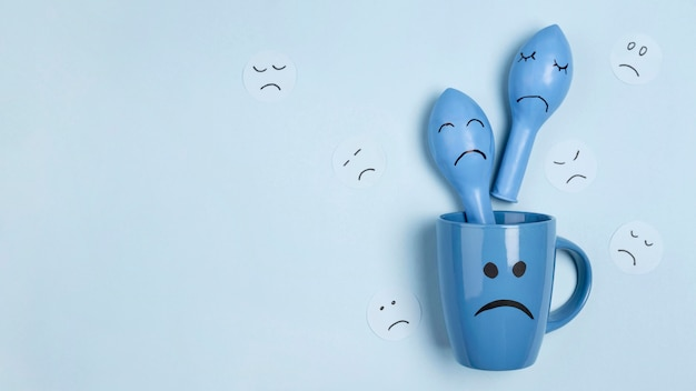 Bovenaanzicht van trieste mok met ballonnen met frons voor blauwe maandag en kopie ruimte