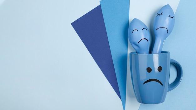 Bovenaanzicht van trieste mok met fronsende ballonnen voor blauwe maandag