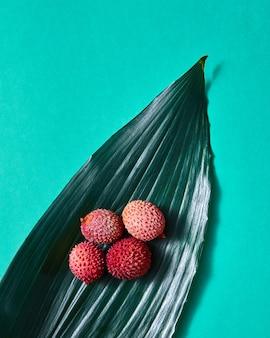 Bovenaanzicht van tropisch exotisch lycheesfruit met groenblijvende bladeren met een grafische gestreepte textuur geïsoleerd