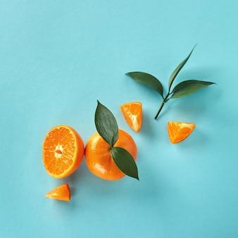 Bovenaanzicht van tropische exotische citrusvruchten mandarijn geheel en plakjes met groene bladeren op een achtergrond van blauw papier
