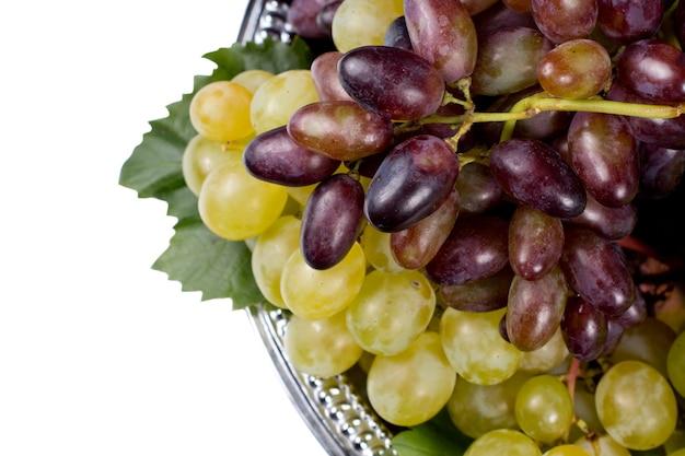 Bovenaanzicht van trossen verse rode en groene druiven op een metalen dienblad, geïsoleerd op wit