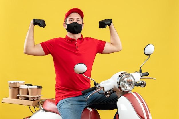 Bovenaanzicht van trotse jonge volwassene die rode blouse en muts handschoenen in medisch masker draagt ?? die orde op scooter levert die zijn spier toont
