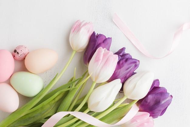 Bovenaanzicht van tulpen met kleurrijke paaseieren