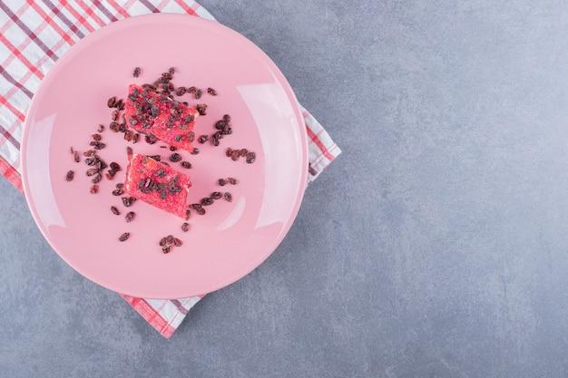 Bovenaanzicht van turks fruit rahat lokum en droge rozijnen op roze plaat.