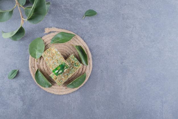 Bovenaanzicht van turks fruit rahat lokum met hazelnoten en decoratieve bladeren op grijze achtergrond.