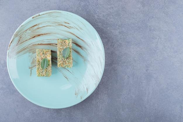 Bovenaanzicht van turks fruit rahat lokum met hazelnoten op blauw bord over grijze achtergrond.
