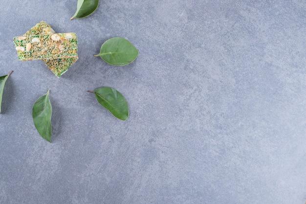 Bovenaanzicht van turks fruit rahat lokum met hazelnoten op grijze achtergrond.