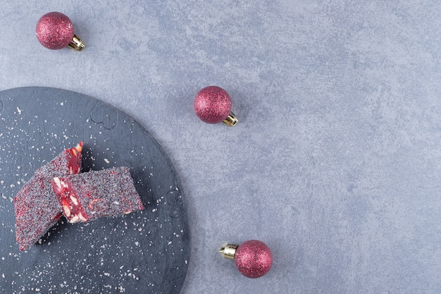 Bovenaanzicht van turks fruit rahat lokum over zwarte houten plank.