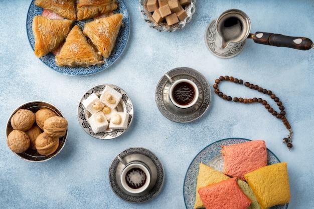Bovenaanzicht van turkse baklava-snoepjes en turkse koffie op lichtblauwe achtergrond