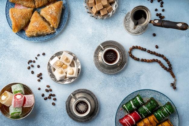 Bovenaanzicht van turkse zoetigheden en turkse koffie op lichtblauwe achtergrond