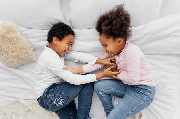 Bovenaanzicht van twee broers en zussen spelen in bed thuis