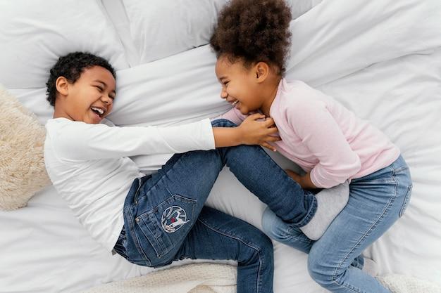 Bovenaanzicht van twee broers en zussen spelen samen in bed thuis