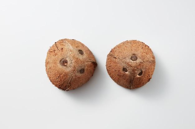 Bovenaanzicht van twee delen van natuurlijke organische bruin exotisch fruit kokosnoten op een lichtgrijze achtergrond met zachte schaduwen en kopieer ruimte. vegetarisch concept.