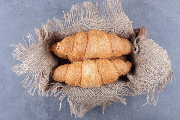 Bovenaanzicht van twee franse croissants in houten kist.