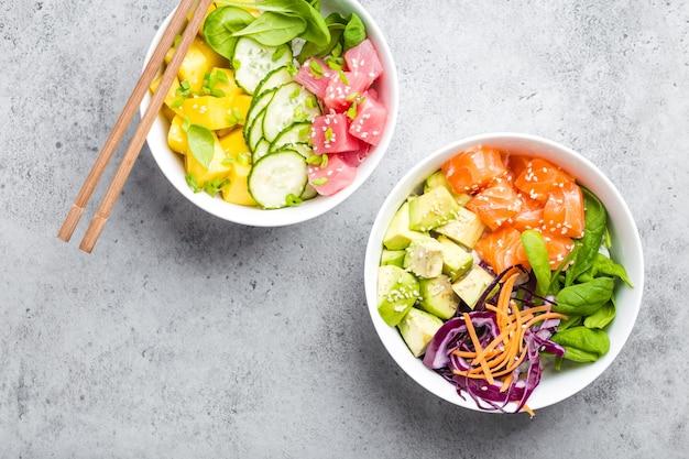Bovenaanzicht van twee geassorteerde poke bowls met verse rauwe tonijn, zalm, groenten, fruit. traditionele hawaiiaanse schotel op rustieke stenen achtergrond. gezond en schoon eten concept. poke met plakjes rauwe vis