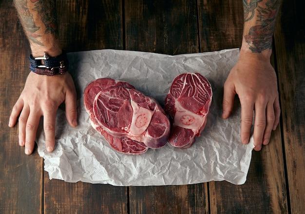 Bovenaanzicht van twee getatoeëerde handen en drie steaks op wit kraftpapier op oude houten tafel