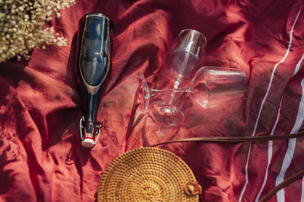 Bovenaanzicht van twee glazen en een fles rode wijn op de rode deken