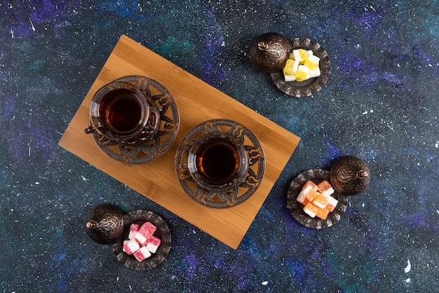 Bovenaanzicht van twee glazen thee en snoep