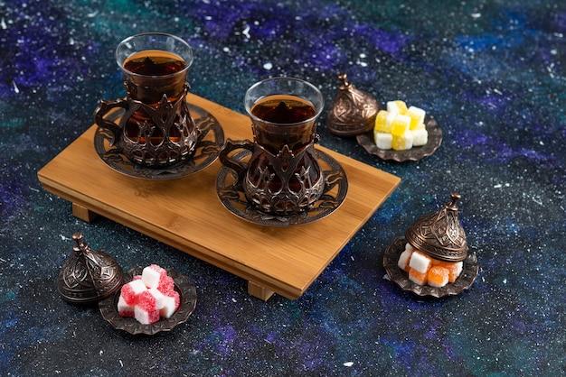 Bovenaanzicht van twee glazen thee op een houten bord en snoepjes op blauwe ondergrond
