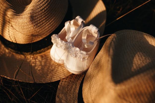 Bovenaanzicht van twee gouden hoeden en een paar babyschoentjes ertussen liggend op gras