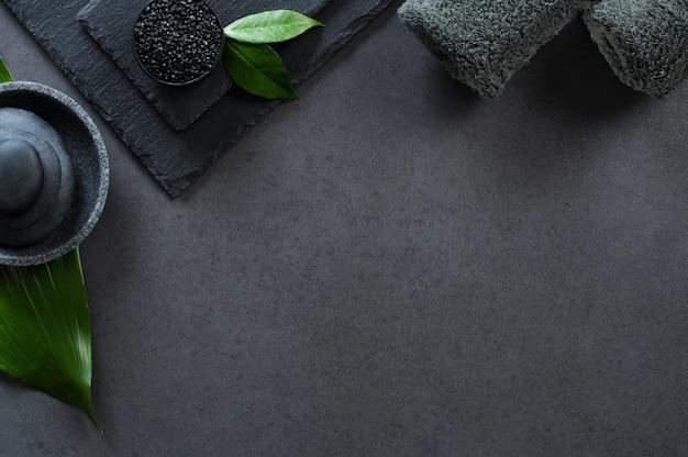 Bovenaanzicht van twee grijze opgerolde handdoeken met hete stenen stapel met kopie ruimte.