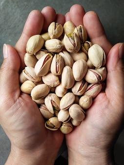 Bovenaanzicht van twee handen houden geroosterde pistaches