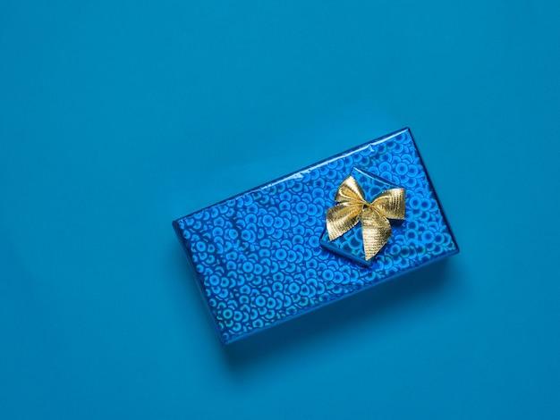 Bovenaanzicht van twee heldere geschenkdozen op een blauwe ondergrond