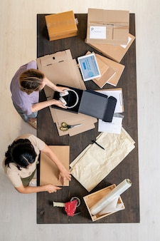 Bovenaanzicht van twee jonge vrouwelijke managers van een online winkel die aan tafel staan en bestellingen van klanten in dozen inpakken tijdens het werk in de opslagruimte store